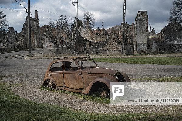 Veraltetes Auto am Straßenrand gegen verlassene Gebäude in Oradour-sur-Glane Veraltetes Auto am Straßenrand gegen verlassene Gebäude in Oradour-sur-Glane