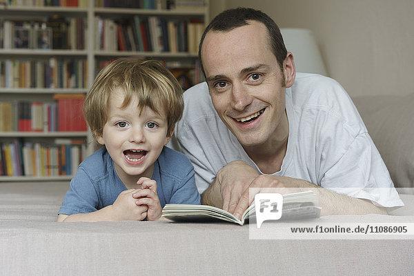 Porträt von lächelndem Vater und Sohn auf dem Bett liegend mit Buch zu Hause