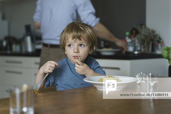 Junge isst Nudeln  während Vater zu Hause in der Küche arbeitet.