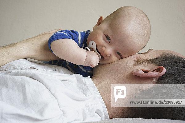 Nahaufnahme des Vaters  der den Sohn hält  während er zu Hause auf dem Bett liegt.
