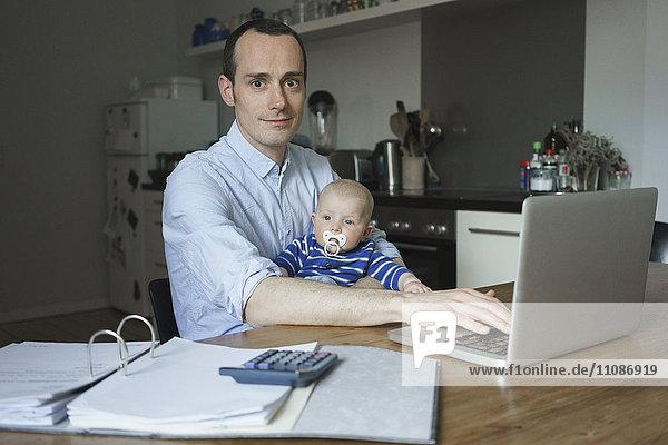 Porträt des Vaters mit Laptop beim Tragen des Sohnes zu Hause