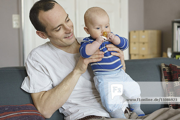 Father carrying toddler and sitting on sofa at home