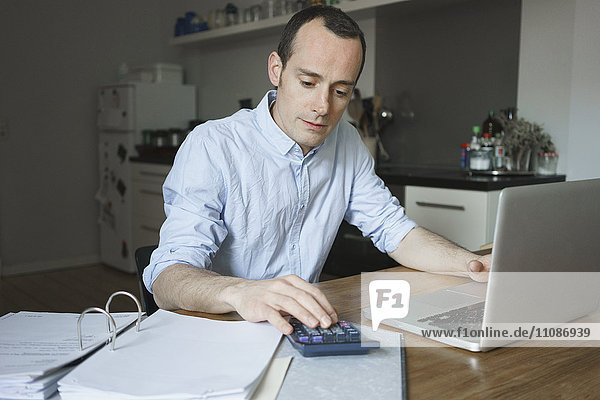 Serious man working over documents with laptop and calculator at home