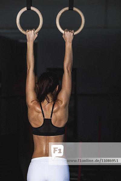 Rückansicht der Frau beim Training mit Gymnastikringen im Fitnessstudio