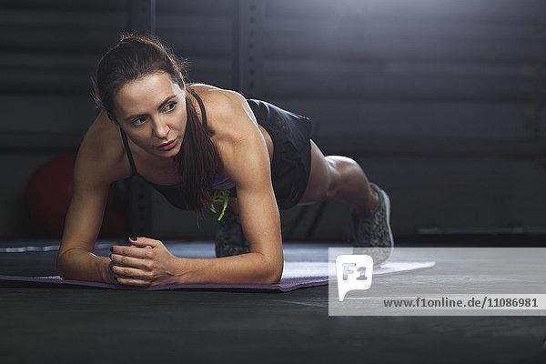 Frau schaut weg  während sie im Fitnessstudio auf der Matte trainiert.