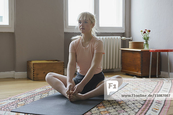 Woman exercising yoga on mat at home