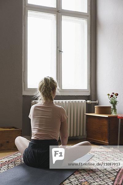 Rückansicht der Frau beim Yoga im Wohnzimmer