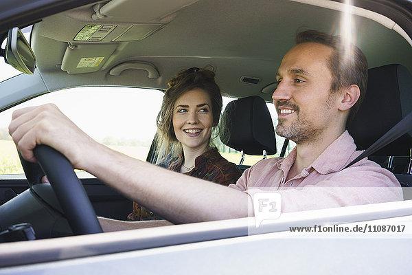 Glückliches Paar  das am Wochenende im Auto unterwegs ist.