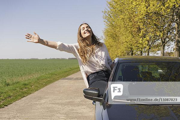 Fröhliche Frau auf dem Autofenster am Straßenrand sitzend