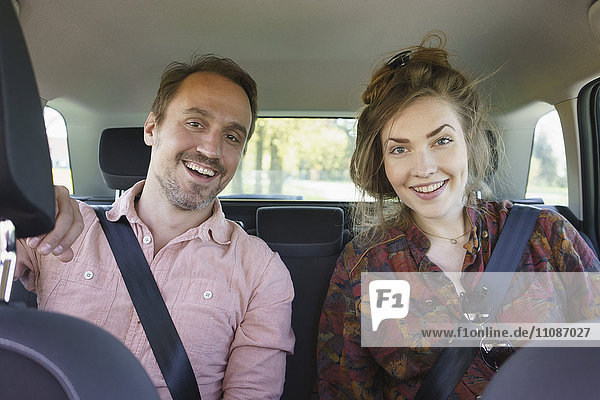 Porträt des glücklichen Paares im Auto sitzend