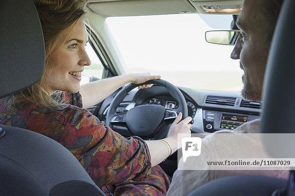 Ein glückliches Paar schaut sich an  während es im Auto unterwegs ist.