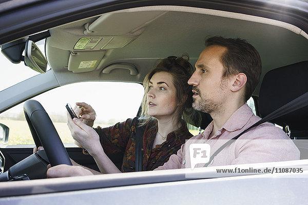Paar mit Handy zur Richtungskontrolle im Auto