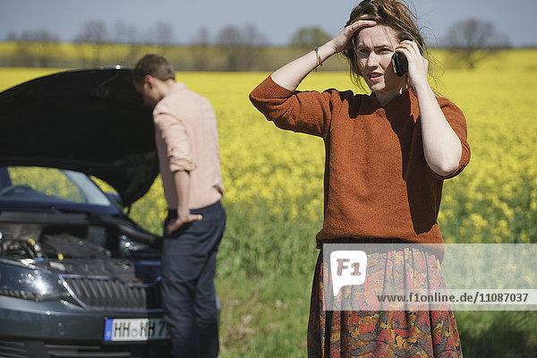 Besorgte Frau spricht am Telefon  während der Mann das Auto im Hintergrund an einem sonnigen Tag repariert.
