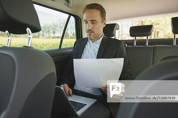 Geschäftsmann hält Dokument  während er den Laptop im Auto benutzt.