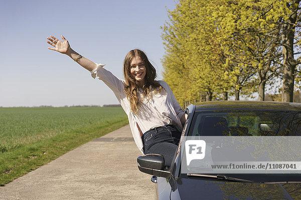 Porträt einer fröhlichen Frau  die am Straßenrand auf dem Autofenster sitzt