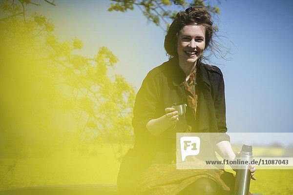 Porträt einer glücklichen Frau  die an einem sonnigen Tag auf dem Autodach sitzt und einen isolierten Getränkebehälter hält.