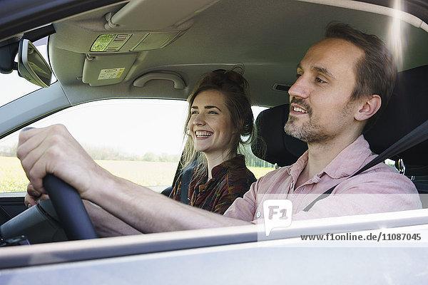 Glücklicher Mann  der neben einer Frau im Auto sitzt.