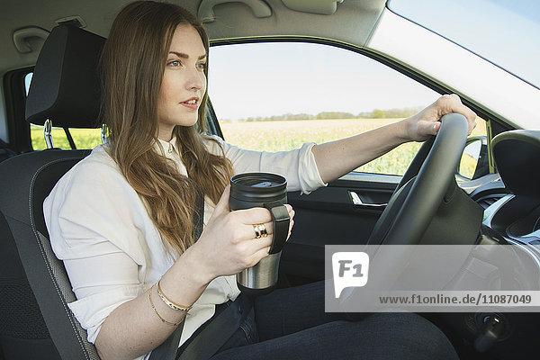 Geschäftsfrau mit isoliertem Getränkebehälter beim Autofahren
