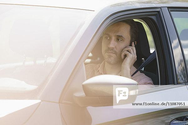 Mann spricht am Handy  während er an einem sonnigen Tag Auto fährt.