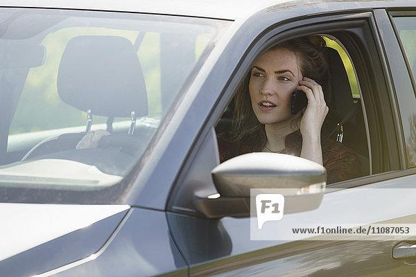 Frau beim Autofahren am sonnigen Tag auf dem Mobiltelefon