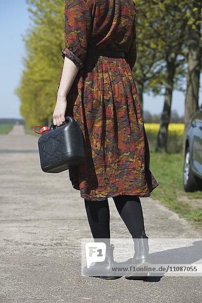 Niedrige Sektion einer jungen Frau  die mit dem Auto auf der Straße steht und Gas hält.