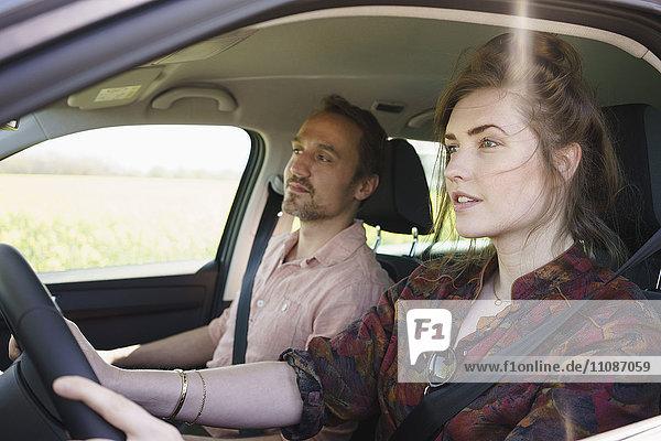 Weibliches Fahren im Sitzen neben dem Mann im Auto
