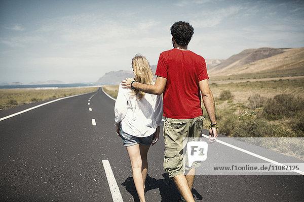Rückansicht des Paares mit Arm um die Straße herum
