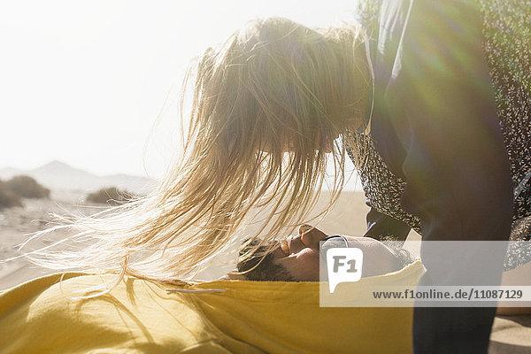 Romantische junge Frau beim Anblick eines Mannes  der im Sommer auf Sand liegt.