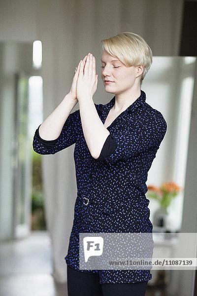 Schöne mittlere erwachsene Frau in Gebetsposition zu Hause