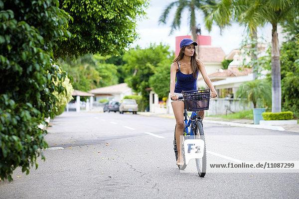 Mexiko  Nayarit  junge Frau beim Radfahren auf der Straße