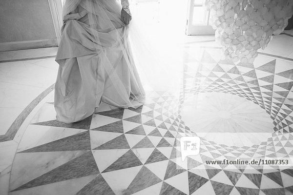 Niedriger Teil der Braut auf gemustertem Boden stehend