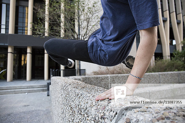 Spain  Madrid  man jumping over a wall in the city during a parkour session