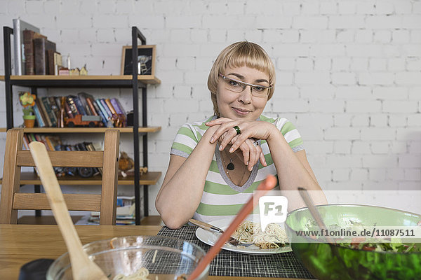 Porträt einer lächelnden Frau mit Spaghetti beim Sitzen am Tisch