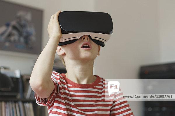 Boy wearing virtual reality simulator at home
