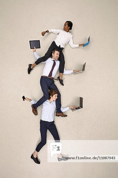 Geschäftsfrau mit Kollegen auf den Schultern bei der Arbeit an mobilen Geräten