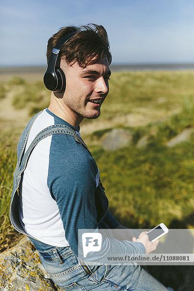 Entspannter junger Mann beim Musikhören mit kabellosen Kopfhörern in der Natur