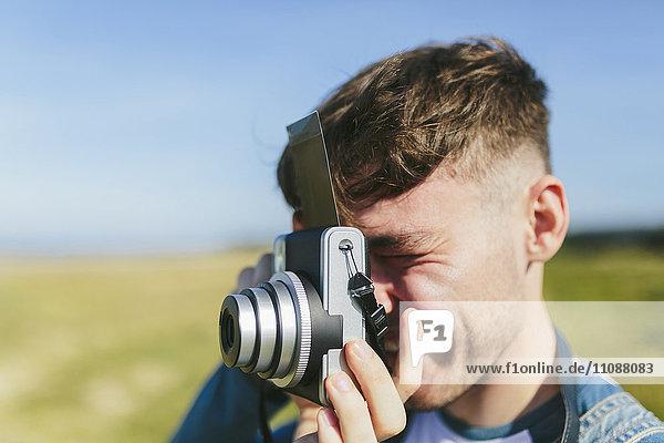 Junger Mann fotografiert mit Polaroidkamera