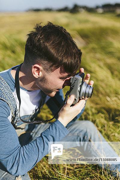 Junger Mann fotografiert mit Kamera