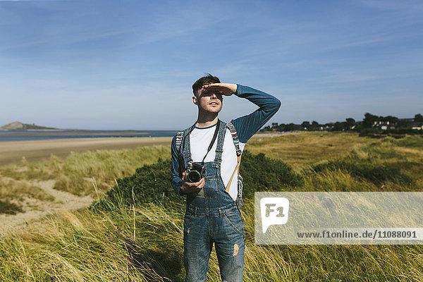 Entspannter junger Mann mit Kamera  der auf einer Düne steht und in die Ferne schaut.