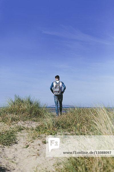 Rückansicht eines jungen Mannes auf einer Düne