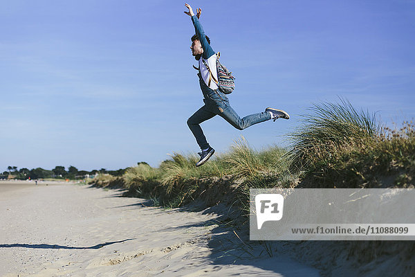 Junger Mann  der am Strand in die Luft springt.
