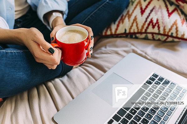Junge Frau sitzt auf Bett  Kaffeetasse  Laptop und Smartphone