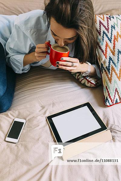 Junge Frau sitzend auf Bett  Kaffeetasse  digitalem Tablett und Smartphone