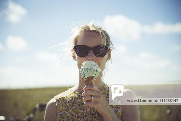 Blonde Frau mit Sonnenbrille beim Eis essen