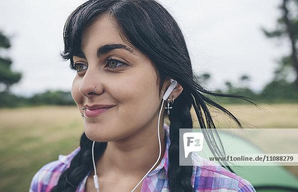 Porträt einer lächelnden jungen Frau mit Piercings beim Musikhören mit Kopfhörern