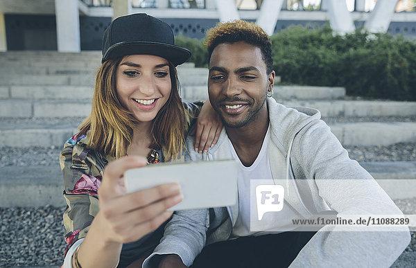 Lächelndes junges Paar sitzt auf einer Treppe und schaut auf das Smartphone.