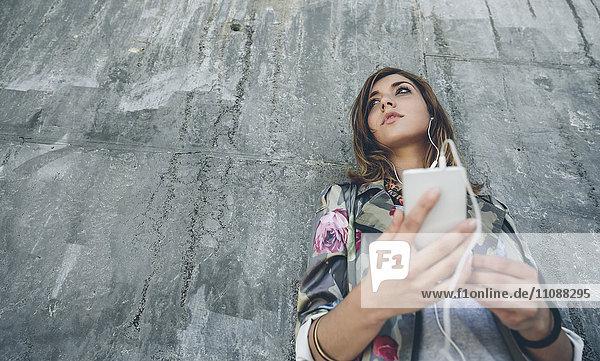 Junge Frau lehnt sich an die Betonwand und hört Musik mit Kopfhörern.