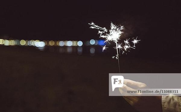 Männerhand hält nachts Wunderkerze am Strand