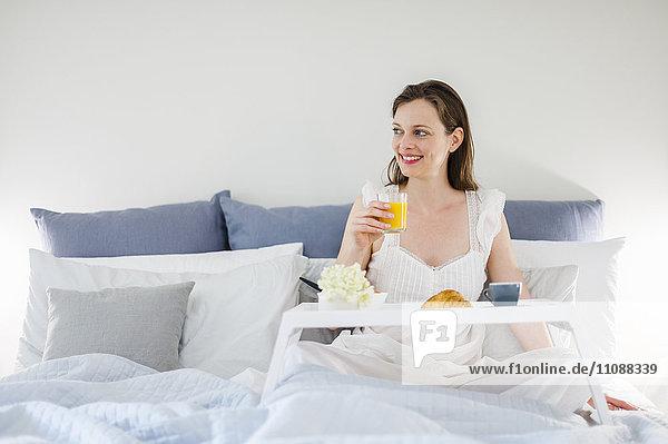 Frau im Bett sitzend mit Frühstückstablett