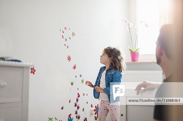 Girl looking at decorated wall in children's room